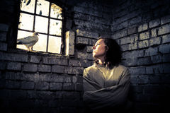 Woman and white dove in prison as a symbol of dreams of freedom Royalty Free Stock Photo