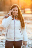 Woman in white down jacket talking on the phone in sunlight Royalty Free Stock Photo