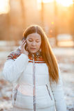 Woman in white down jacket talking on phone in the sunlight Stock Images