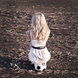Woman in white drees sit on ball. Football game Royalty Free Stock Photography