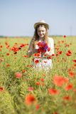 Woman at white dress adjust poppy bouquet Stock Image