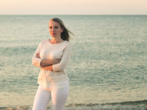 Woman in white dress against the evening the calm sea. Royalty Free Stock Images
