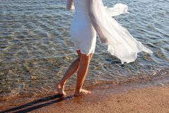 Woman in white dress back walking on beach Royalty Free Stock Photos
