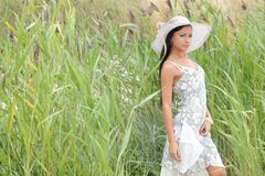 woman in a white dress on a background of tall grass Royalty Free Stock Photo