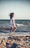 Woman in a white dress on the beach Royalty Free Stock Photo