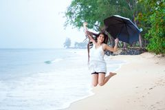 Woman in white dress on beach holding umbrella enjoying rain Royalty Free Stock Photos
