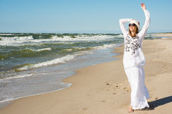 Woman in white dress dancing near the sea Stock Images