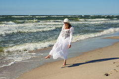 Woman in white dress dancing near the sea Royalty Free Stock Image