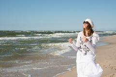 Woman in white dress dancing near the sea Stock Image