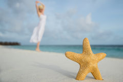 Woman in a white dress dancing on the tropical beach against starfish closeupops closeup. Woman in a white dress dancing on the tropical beach against starfish Stock Photo