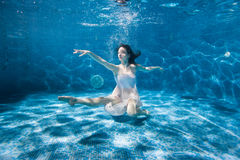 Woman white dress dancing underwater in the pool. Woman in a white dress is dancing under the water in the pool, sports dancing Stock Photos