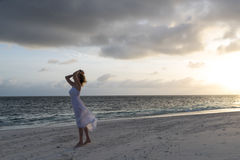 Woman in white Dress at dark sea. Stock Photo