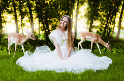 Woman in white dress with deers. On nature Royalty Free Stock Image