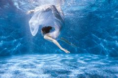 Woman in a dress under the water. Woman in a white dress dives under the water in the pool stock photography