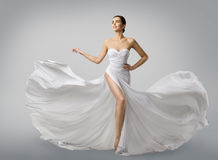 Woman White Dress, Fashion Model Bride in Long Silk Wedding Gown. Elegant Flying Fabric, Fluttering Cloth royalty free stock photos