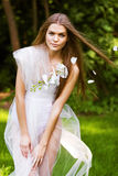 Woman in white dress and flying petals Stock Photography