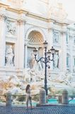 Woman in white dress  in front of Trevi Fountain in Rome Stock Photo