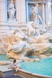 Woman in white dress  in front of Trevi Fountain in Rome Stock Photos