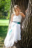 Woman in white dress in green park sitting on tree. eco green concept. Stock Photography