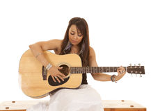 Woman white dress guitar sit and strum. A woman looking down at her guitar playing a song royalty free stock images