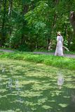 Woman in a white dress and hat goes along the shore of a pond Royalty Free Stock Photos
