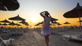 Woman on tropical beach at sunset. Woman in white dress and hat walk toward camera on beach in the seaside resort with sun loungers and wooden sheds against stock image