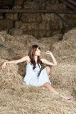 Woman in white dress on haystack Stock Images