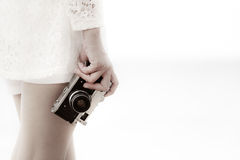 Woman in white dress holding old vintage camera Stock Photo