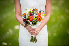Woman in White Dress Holding Orange and Green Bouquet of Flower Stock Images