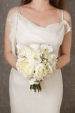 Woman in a white dress holding white bouquet with peonies, carna Royalty Free Stock Photography