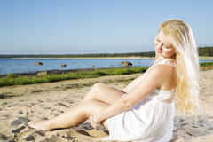 Woman in white dress indulgence on sand Stock Images