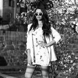 Woman in white dress and jacket posing against blooming shrub on background. Young slim female model with long wavy hair and sunglasses dressed in white dress Stock Image