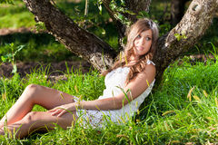 Woman in white dress leaning to tree trunk at park Stock Images