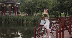 Woman in white dress looking at camera while riding in park stock video footage