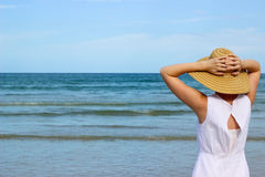 Woman In White Dress Looking At Ocean. Woman in white dress and straw hat with with hands on head looking out at the ocean at the beach Royalty Free Stock Image