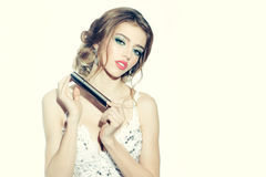 Woman in white dress with makeup tool Royalty Free Stock Photography