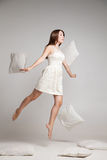Woman in white dress in mid air with flying pillows. Studio shot of weightless woman jumping with flying pillows Stock Photo