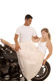 Woman in white dress on motorcycle man stand behind Stock Photography