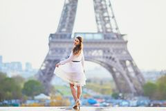 Woman in white dress near the Eiffel tower in Paris, France Stock Image