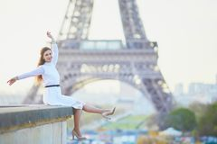 Woman in white dress near the Eiffel tower in Paris, France. Happy young woman in white dress near the Eiffel tower in Paris, France Stock Photo