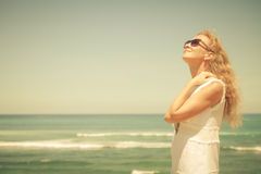 Woman in a white dress on the ocean coast Stock Photo
