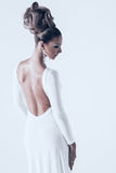 Woman in white dress with opened back. In studio Stock Photos