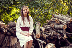 Woman in white dress in park on logs of trees Stock Photo