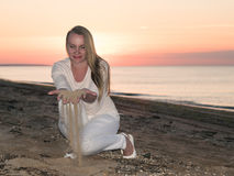 Woman in white dress plays with sand in the sunset. Royalty Free Stock Images