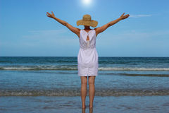 Woman In White Dress Raising Arms Looking At Ocean. Woman in white dress and straw hat standing on the beach with arms raised looking out at the ocean with sun Stock Images