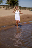 Woman white dress run to water Royalty Free Stock Photos