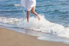 Woman in white cotton dress run through water on sandy sea beach sunny summer day lower body back view. Woman in white dress run through water on sandy sea beach royalty free stock image