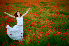 Woman in white dress running poppy field royalty free stock photography
