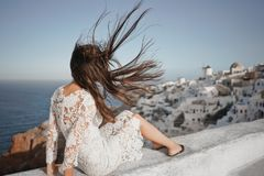 Woman in white dress on Santorini island. Happy woman in white dress enjoying her holidays on Santorini island. View on Aegean sea from Oia. Europe summer travel Royalty Free Stock Photos