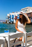 Woman in white dress sits in front of Little Venice in Mykonos. Woman in white dress and har sits in front of Little Venice in Mykonos, Greece Stock Image